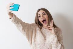 La muchacha adolescente con el pelo largo hace el teléfono del selfie Fotografía de archivo