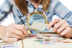La muchacha adolescente con la lupa mira su colección de sello Fotos de archivo
