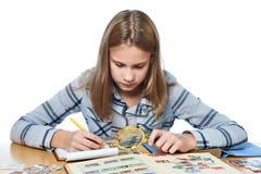 La muchacha adolescente con la lupa mira su colección de sello aislada Foto de archivo