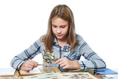 La muchacha adolescente con la lupa mira su colección de sello aislada Imagenes de archivo