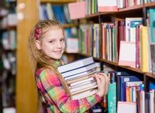 La muchacha adolescente con la pila reserva en la biblioteca Foto de archivo