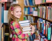 La muchacha adolescente con la pila reserva en la biblioteca Fotografía de archivo
