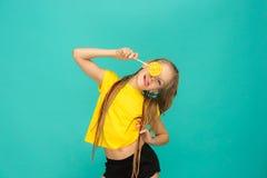 La muchacha adolescente con la piruleta colorida en un fondo azul Imágenes de archivo libres de regalías