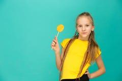 La muchacha adolescente con la piruleta colorida en un fondo azul Fotos de archivo