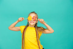 La muchacha adolescente con la piruleta colorida en un fondo azul Fotografía de archivo libre de regalías