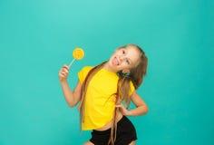 La muchacha adolescente con la piruleta colorida en un fondo azul Imagen de archivo libre de regalías