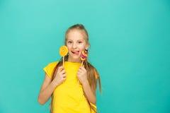 La muchacha adolescente con la piruleta colorida en un fondo azul Foto de archivo