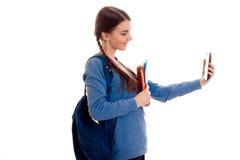 La muchacha adolescente con las coletas guarda una mochila en el suyo parte posterior y fotografiado en el teléfono que da vuelta Fotografía de archivo