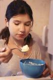 La muchacha adolescente con los auriculares come del refrigerador Fotografía de archivo libre de regalías