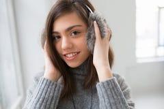La muchacha adolescente con los auriculares mullidos escucha música Imágenes de archivo libres de regalías