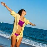 La muchacha adolescente con los brazos se abre en la playa. Imagenes de archivo