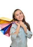 La muchacha adolescente con los paquetes multicolores en manos disfruta compras Fotografía de archivo