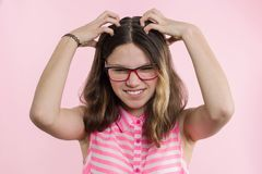 La muchacha adolescente con los vidrios, con el pelo largo rasguña su cabeza y es emocional desconcertada Imagen de archivo