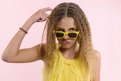 La muchacha adolescente con los vidrios, con el pelo largo rasguña su cabeza y es emocional desconcertada Fotos de archivo libres de regalías