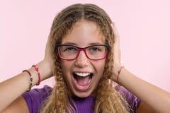 La muchacha adolescente con los vidrios, con el pelo largo rasguña su cabeza y es emocional desconcertada Fondo rosado del estudi Foto de archivo libre de regalías