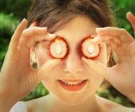 La muchacha adolescente con mitad cortada de la fruta del rambutan observa Imágenes de archivo libres de regalías