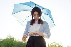 La muchacha adolescente con un paraguas mira el reloj Imagenes de archivo