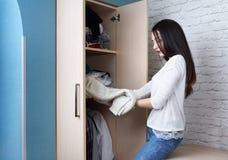 La muchacha adolescente consigue la ropa con el guardarropa Fotografía de archivo