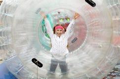 La muchacha adolescente corre feliz dentro de un cilindro-zorb inflable grande Foto de archivo libre de regalías