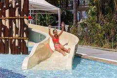 La muchacha adolescente de risa alegre va abajo por el tobogán acuático en el aquapark del hotel fotografía de archivo