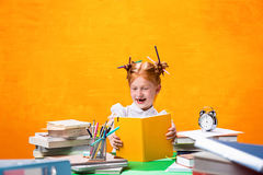 La muchacha adolescente del pelirrojo con la porción de libros en casa Tiro del estudio Foto de archivo