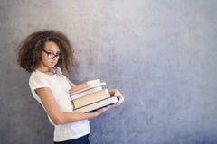 La muchacha adolescente del pelo rizado con los vidrios se coloca al lado de la pared y ho Fotografía de archivo