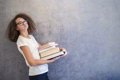 La muchacha adolescente del pelo rizado con los vidrios se coloca al lado de la pared y ho Imagenes de archivo