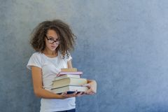 La muchacha adolescente del pelo rizado con los vidrios se coloca al lado de la pared y ho Imagen de archivo