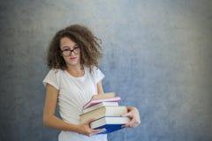La muchacha adolescente del pelo rizado con los vidrios se coloca al lado de la pared y ho Imágenes de archivo libres de regalías