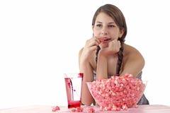 La muchacha adolescente disfruta de las palomitas y de la bebida rosadas Fotografía de archivo libre de regalías