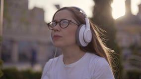 La muchacha adolescente divertida escucha la música en los auriculares y canta a lo largo de 4K almacen de metraje de vídeo
