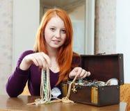 La muchacha adolescente elige la joyería en cofre del tesoro Fotografía de archivo