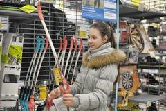 la muchacha adolescente elige un arco para la tienda de los deportes que tira Fotografía de archivo