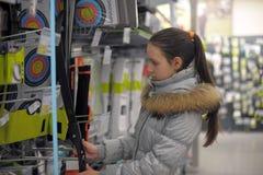 la muchacha adolescente elige un arco para la tienda de los deportes que tira Fotos de archivo