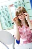 La muchacha adolescente elige vidrios Fotos de archivo