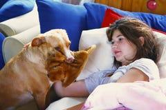 La muchacha adolescente en cama y el perro traen las zapatillas de deporte fotos de archivo