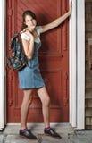 La muchacha adolescente en dril de algodón se inclina contra puerta roja. Imágenes de archivo libres de regalías