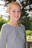 La muchacha adolescente en el jardín está sonriendo en cámara Fotografía de archivo libre de regalías