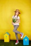 La muchacha adolescente en el sombrero de paja que lleva a cabo la primavera florece Foto de archivo libre de regalías