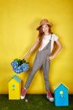 La muchacha adolescente en el sombrero de paja que lleva a cabo la primavera florece Fotografía de archivo