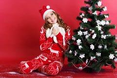 La muchacha adolescente en el sombrero de santa se está sentando cerca de la Navidad Imágenes de archivo libres de regalías
