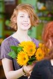 La muchacha adolescente en floristería compra los girasoles Imagen de archivo libre de regalías