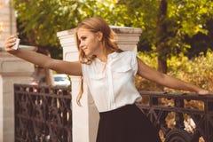 La muchacha adolescente en parque del otoño está tomando el selfie Imagen de archivo libre de regalías