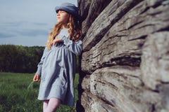 La muchacha adolescente en ropa casual y sombrero azul sueña inclinarse en una pared de madera Forma de vida activa Moda de la ju Foto de archivo libre de regalías