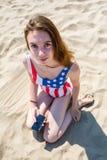 La muchacha adolescente en un traje de baño con una impresión de la bandera de los E.E.U.U. se sienta en la arena con el teléfono Fotografía de archivo libre de regalías
