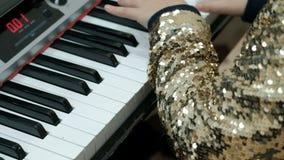 La muchacha adolescente en una blusa de oro brillante juega el piano eléctrico Los fingeres de los niños pulsan las teclas del si almacen de video