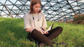 La muchacha adolescente en una camisa gris se sienta en la hierba en el parque mira alrededor y lee un cuaderno con las notas de  almacen de video