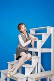 La muchacha adolescente en uniforme escolar se sienta en pasos Fotos de archivo libres de regalías