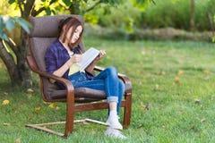 La muchacha adolescente en vaqueros se está sentando en una silla en el jardín con un libro Fotografía de archivo
