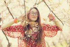 La muchacha adolescente en vidrios acerca al árbol del flor Foto de archivo libre de regalías